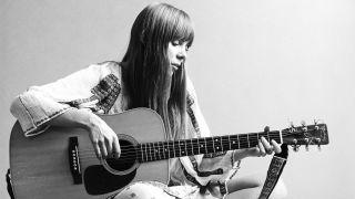 Portrait of Canadian musician Joni Mitchell seated on the floor playing acoustic guitar, November 1968.