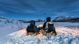 Two people sit in front of a campfire in the snow
