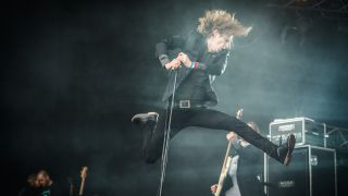 Dennis Lyxzen of Refused leaping into the air onstage