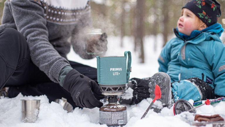 Parent and child using Primus Lite+ stove in the snow