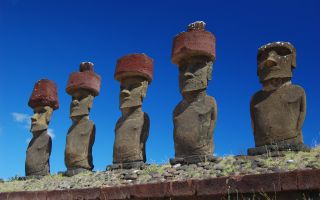 Moai with red topknot hats at Anakena Ahu Na in Chile, Easter Island.