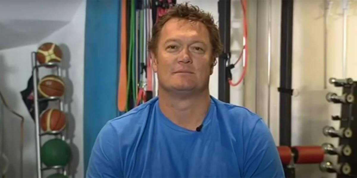Luc Longley being interviewed in his workout room with basketballs and weights in the background.
