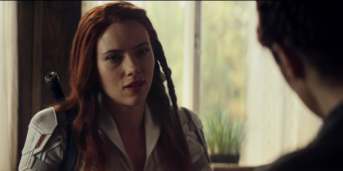Scarlett Johansson sitting with her back to the window while talking in Black Widow.