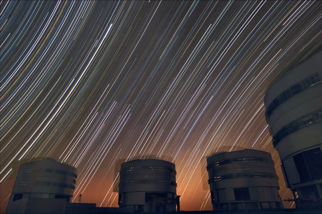 The sky appears to rotate above ESO's Very Large Telescope in this long exposure. The star trails curve away from the celestial equator in the middle of the photo, where the stars seem to move in a straight line.