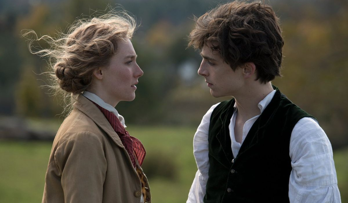 Little Women Saoirse Ronan and Timothee Chalamet stare intensely at each other in a field