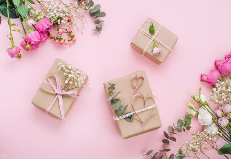 gifts wrapped in brown paper and pink ribbon on a pink background decorated with flowers and foliage