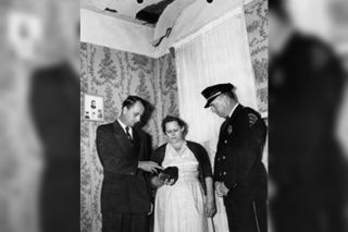 Ann Hodges (center) poses with her meteorite, underneath the point where it crashed through her house, with Sylacauga, Alabama mayor Ed Howard (left) and the town's police chief W.D. Ashcraft. Hodges was struck by the meteorite while on her couch on Nov. 30, 1954. She donated it to the University of Alabama's Museum of Natural History in 1956.