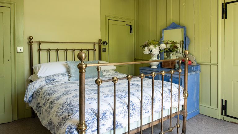 green bedroom with brass bed
