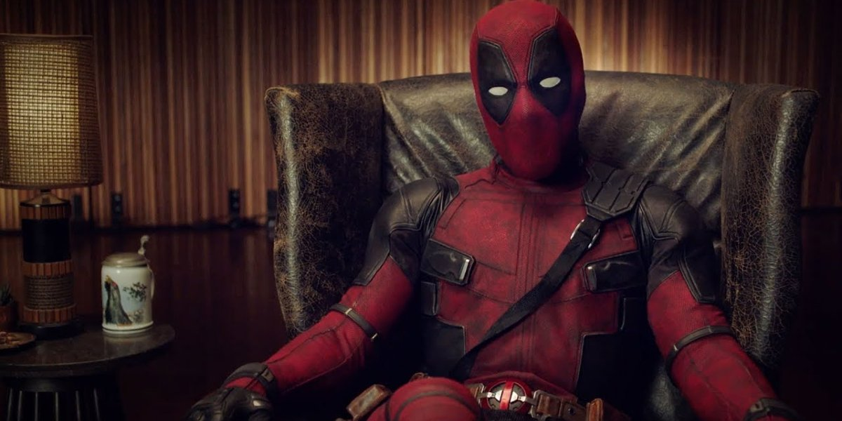 Deadpool sitting in a leather chair, speaking to the audience
