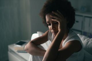 A woman sitting on a bed looking tired.