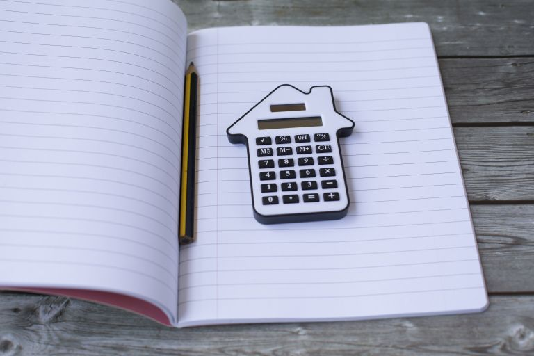 mortgage advisor advice: book with calculator shaped like a house