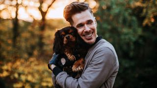 Best dogs for anxiety: man cuddling Cavalier King Charles Spaniel