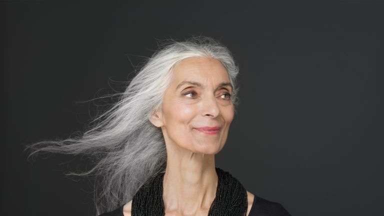 Woman with long grey hair smiling