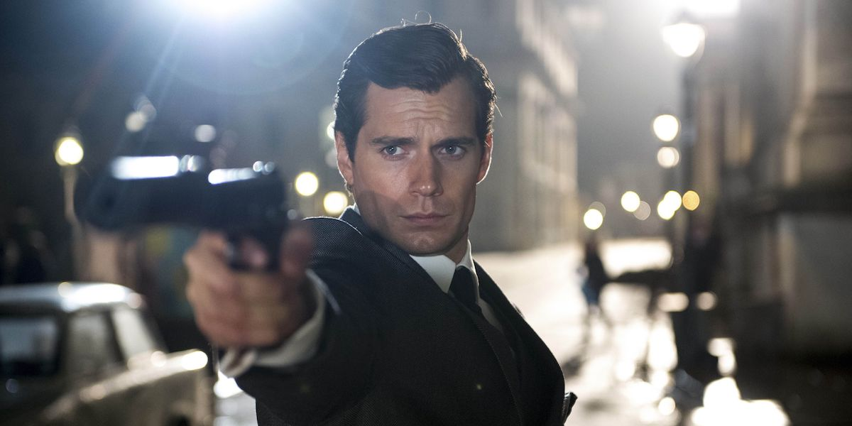 Napoleon Solo (Henry Cavill) points a gun while wearing a suit in 'The Man from U.N.C.L.E.'