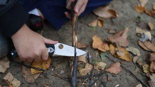 a camping knife cutting a stick
