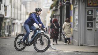 A woman riding a Canyon e-bike through city streets
