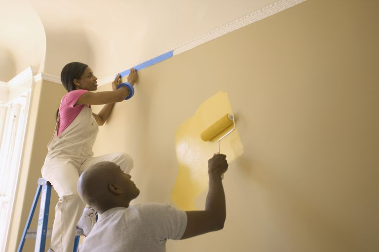 Couple painting a wall lemon yellow with rollers