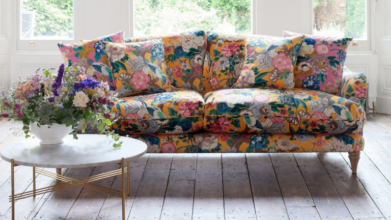 floral sofa on wooden floor with table with flowers