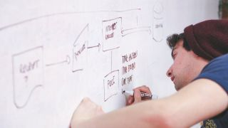Designer writing on a whiteboard