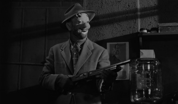 Sterling Hayden with a gun and wearing a clown mask