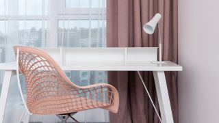 How to clean an office chair: a clean, neutral office chair in front of a white desk