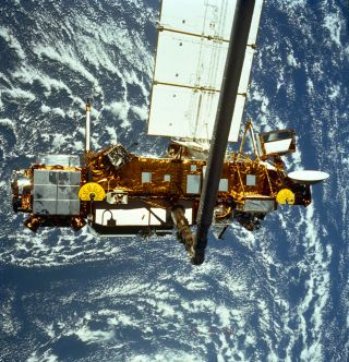 The Upper Atmosphere Research Satellite hangs in the grasp of the Remote Manipulator System during deployment from Space Shuttle Discovery, September 1991.