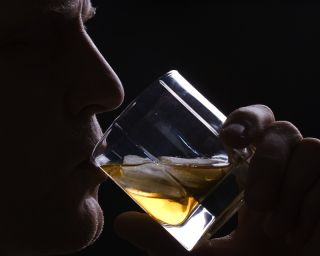 A man drinks a glass of alcohol