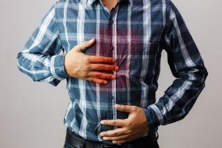 A man feels the pain of heartburn.