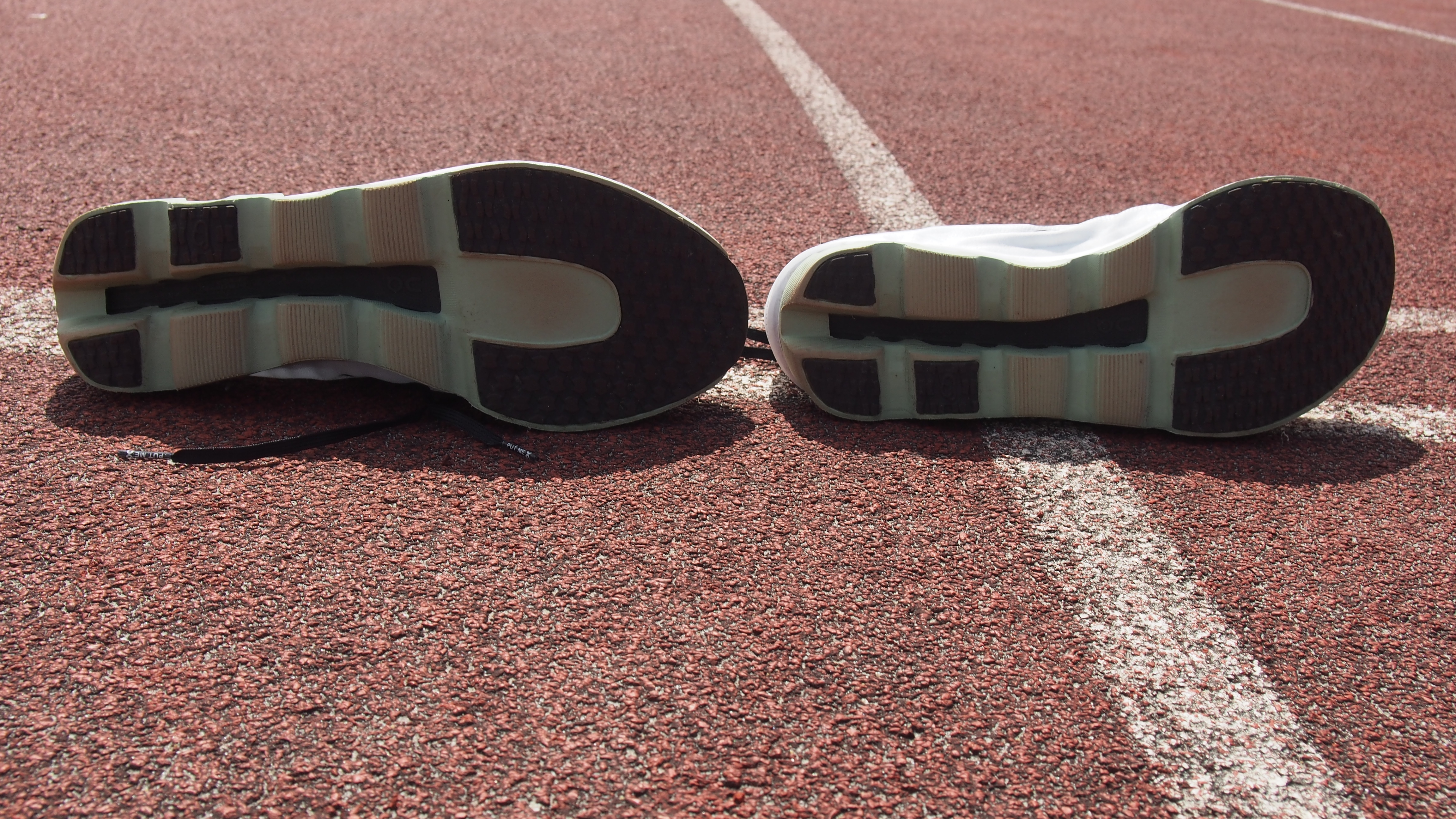 Pair of On Cloudboom Echo running shoes on a running track, with their soles showing