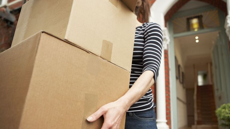 images of woman in striped top collecting packages outside of front door by getty images