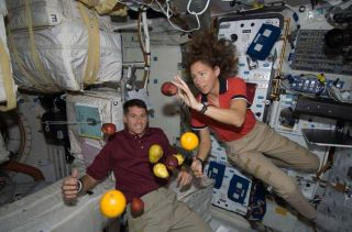 Astronauts Shane Kimbrough and Sandra Magnus, both STS-126 mission specialists, float with fresh fruit aboard Space Shuttle Endeavour on Nov. 16, 2008.