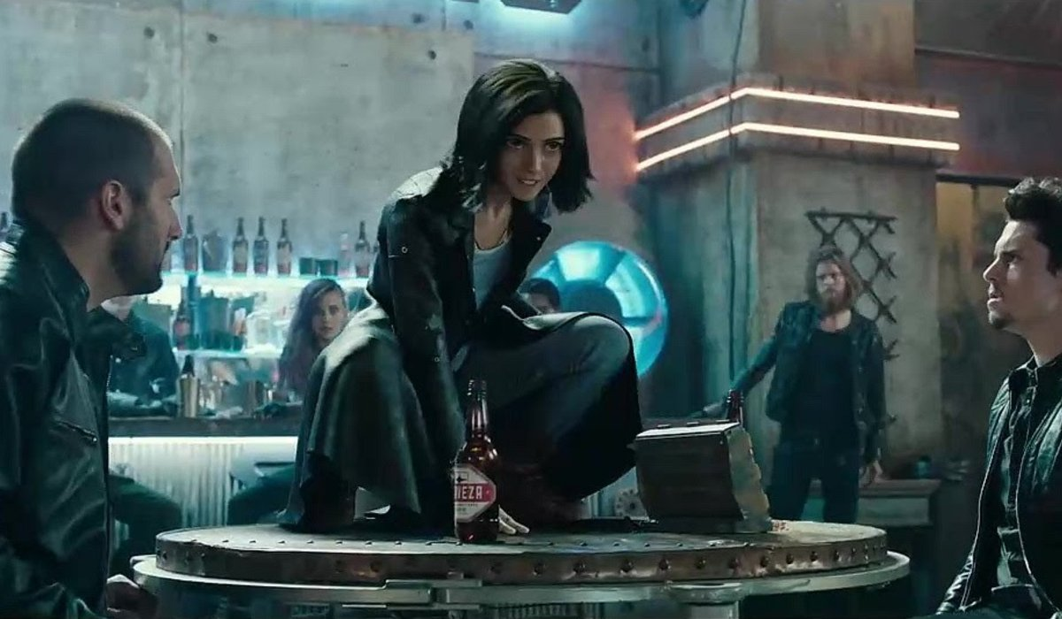 Alita: Battle Angel Alita crouched on a table in the Kansas bar