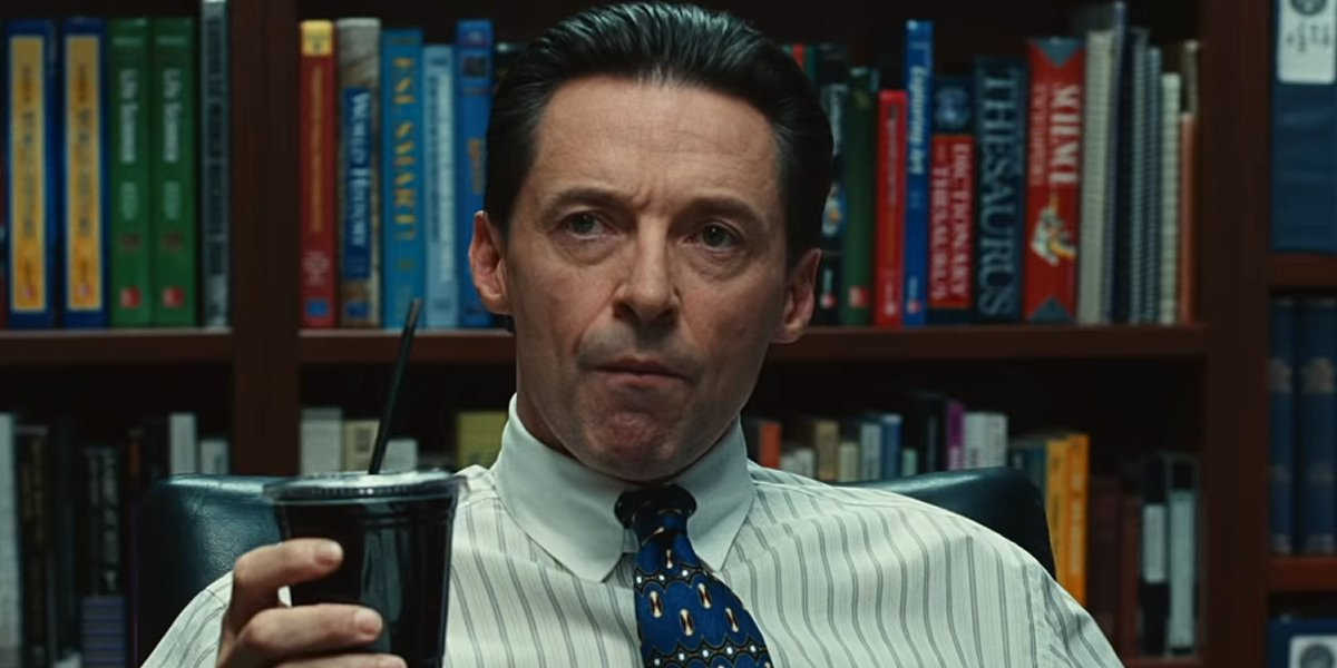 Hugh Jackman pulls a face of surprise with a drink cup in his hand in Bad Education.