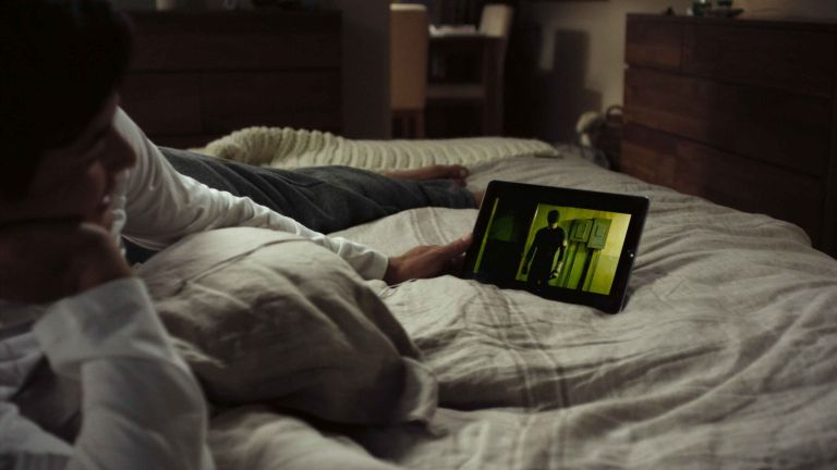 Netflix Series: person on bed watching Netflix on tablet