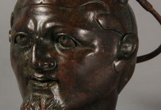 Dating back about 1,800 years, the brass balsamarium shows the head of a man wearing a cap made from the skin of a feline.