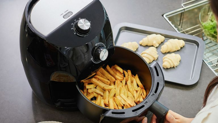 a hand using an air fryer to cook chips