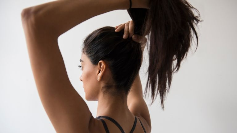 woman tying her hair into a ponytail