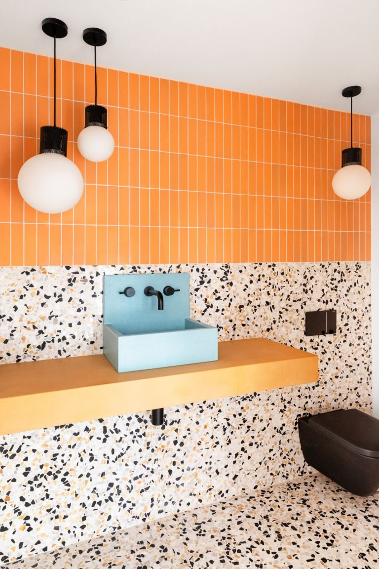 Bright orange small scale vertical metro tiles with terrazzo wall to floor tiling in modern bathroom complete with blue basin and black toilet