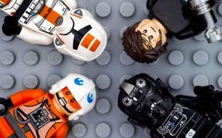 Four Lego Star Wars minifigures - Anakin Skywalker, TIE Pilot, Zev Senesca and Republic Trooper - on Lego gray baseplate background. Studio shot.