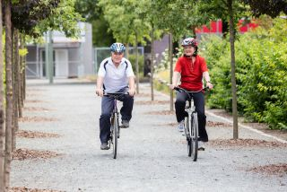 An older couple rides bicycles, wearing helmets.