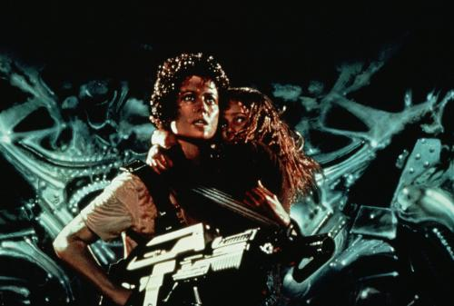 Aliens - Sigourney Weaver's Ripley protects young survivor Newt (Carrie Henn) in James Cameron's sci-fi action blockbuster.