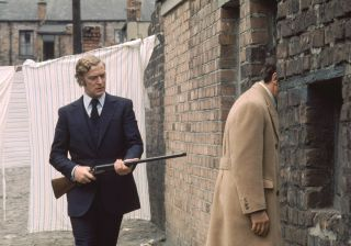 Michael Caine points a shotgun at the back of a man entering a house