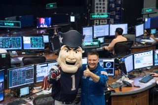 A NASA astronaut poses with Pat Patriot, mascot of the New England Patriots, during a visit to Mission Control in Houston at Johnson Space Center ahead of Super Bowl LI. The Patriots will face off against the Atlanta Falcons during the big game.