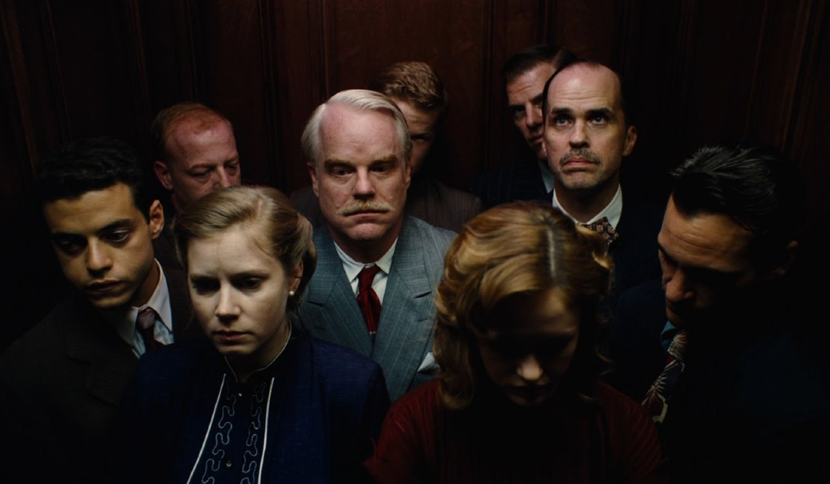 Rami Malek, Amy Adams, Phillip Seymour Hoffman, and Joaquin Phoenix stand in a crowded elevator in The Master.