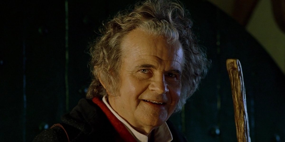 Bilbo Baggins (Ian Holm) smiles while holding his walking stick.