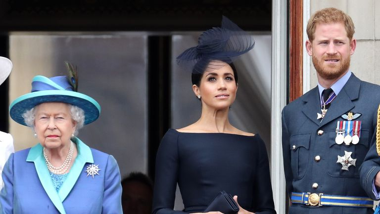 Queen Elizabeth II, Prince Harry, Duke of Sussex and Meghan, Duchess of Sussex on the balcony of Buckingham Palace as the Royal family attend events to mark the Centenary of the RAF on July 10, 2018 in London, England