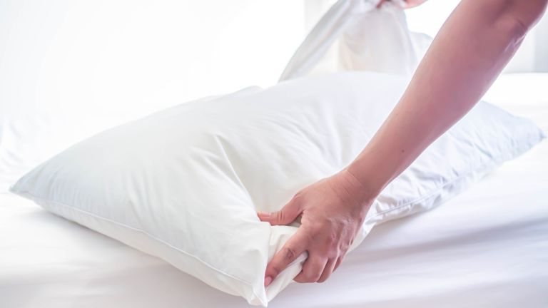 White pillow on the bed in the bedroom with woman 's hand as she is changing her bedsheets