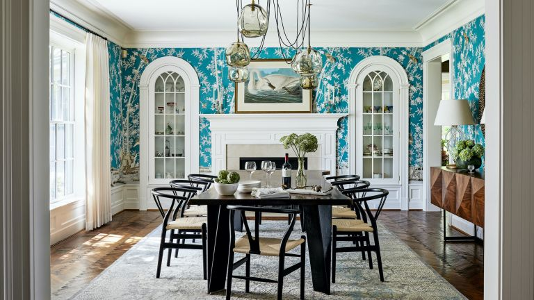 A dining room with turquoise blue and white patterned wallpaper, pendant light with drooping cables, and white arched built-in glass cabinets
