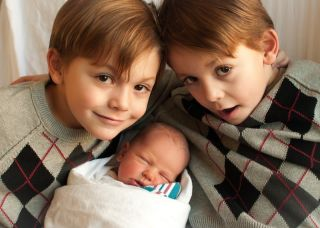 Twin boys with newborn baby.