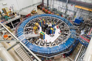 A top view of the equipment used in the g-2 experiment at Fermilab. The experiment uses a muon beamline, electronic racks and superconducting magnetic storage ring cooled to minus 450 degrees Fahrenheit (minus 267 degrees Celsius) to study the wobble of muons.